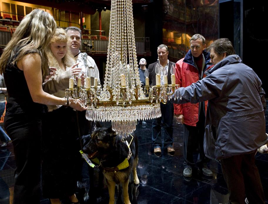 A group of people on a Touch Tour examining a chandelier