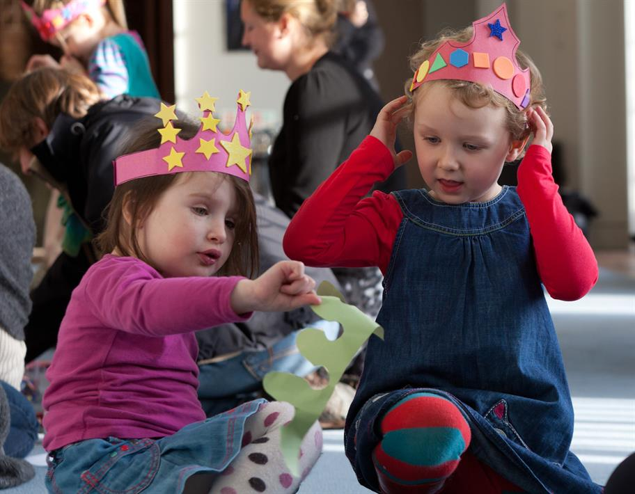 Young children make paper crowns, one of the craft activities in the playcart.