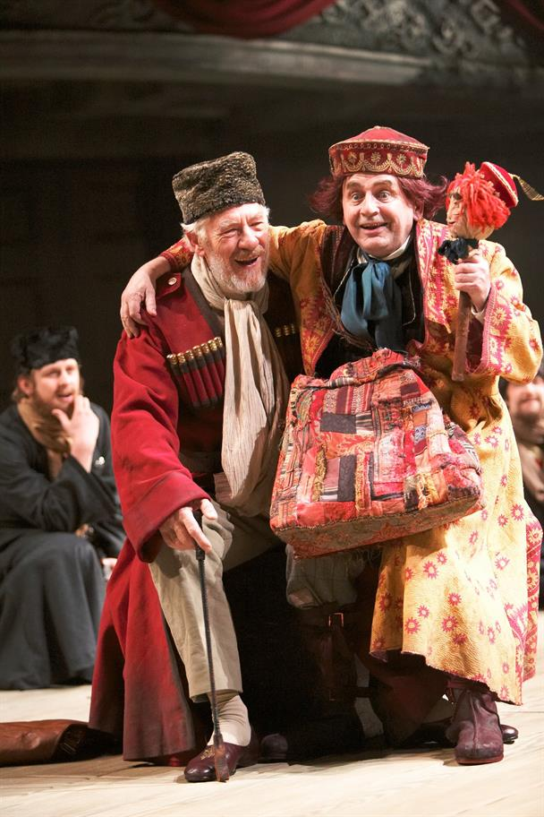 Two men dressed colourfully sit on stage looking merry