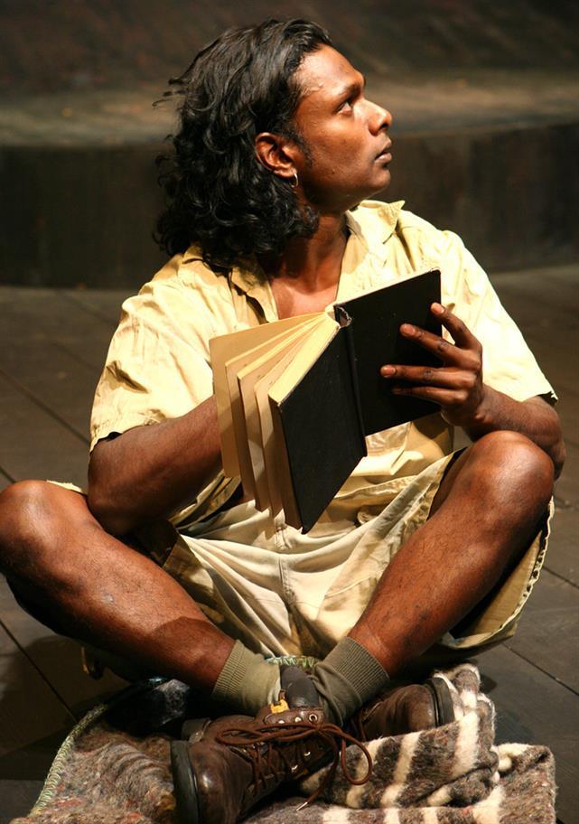 Man sitting on stage cross legged reading