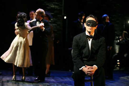 Romeo (David Dawson) sits at the ball while Juliet (Anneika Rose) dances in the background with her father (Christopher Hunter).