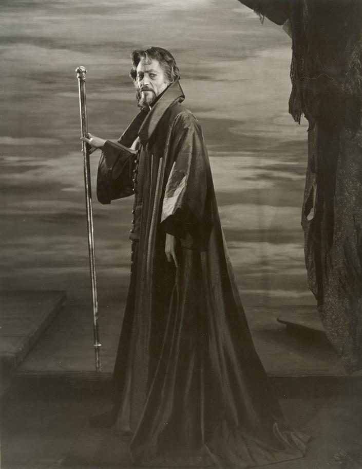 Man wearing long robes holding staff, image is in black and white