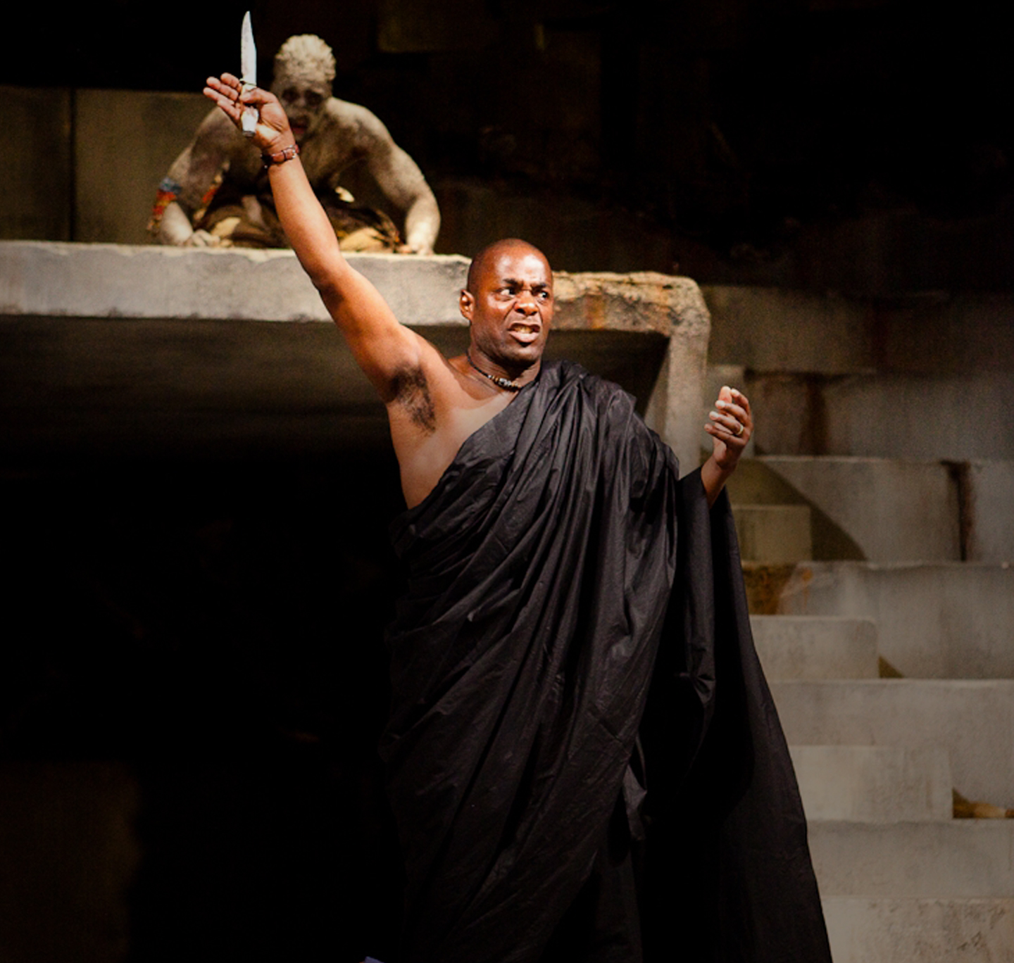 Angry man stands on stage with arm outstretched above his head holding a knife