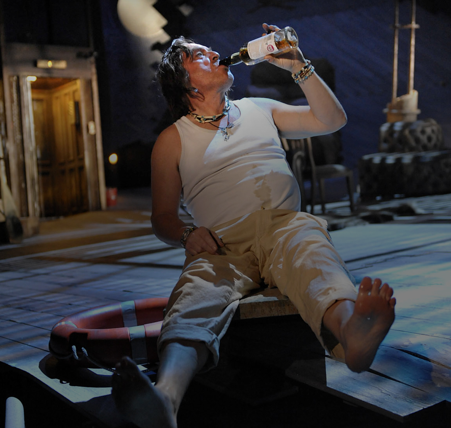 Man sits on stage drinking alcohol