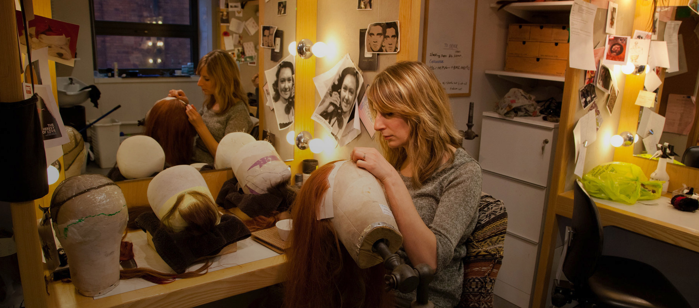 A blonde woman holding a head model and stitching a long red wig in a dressing room full of photos and wigs