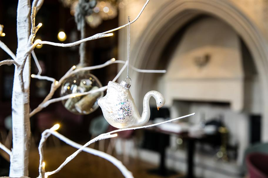 A white Christmas tree branch with a swan ornament and glass bauble
