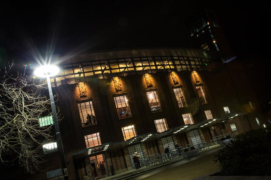 The front of the Royal Shakespeare Theatre lit up at night.