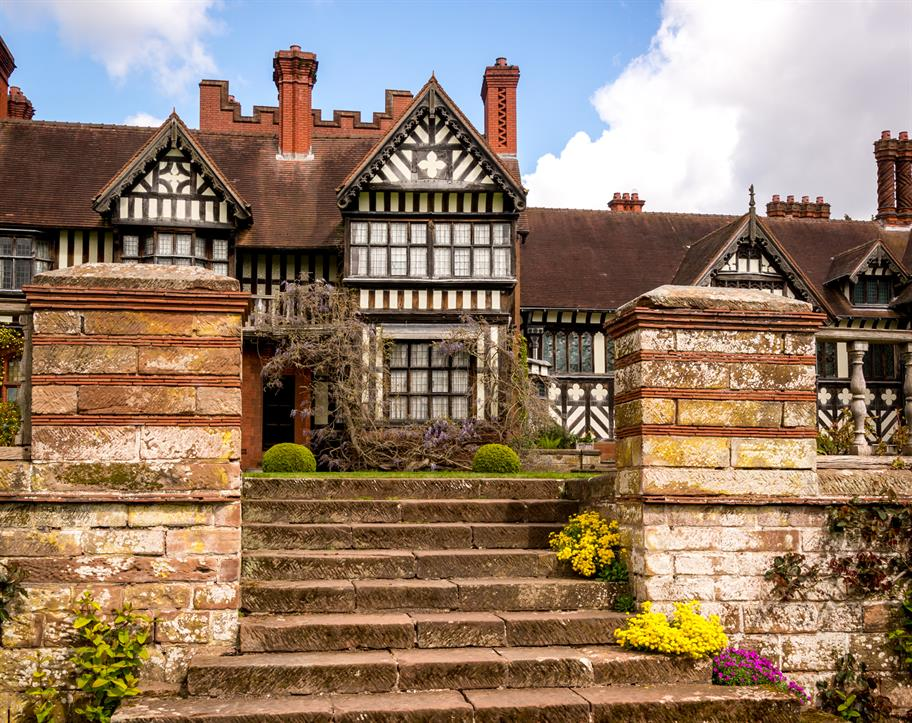 External view of black and white timer mock-Tudor house and gardens