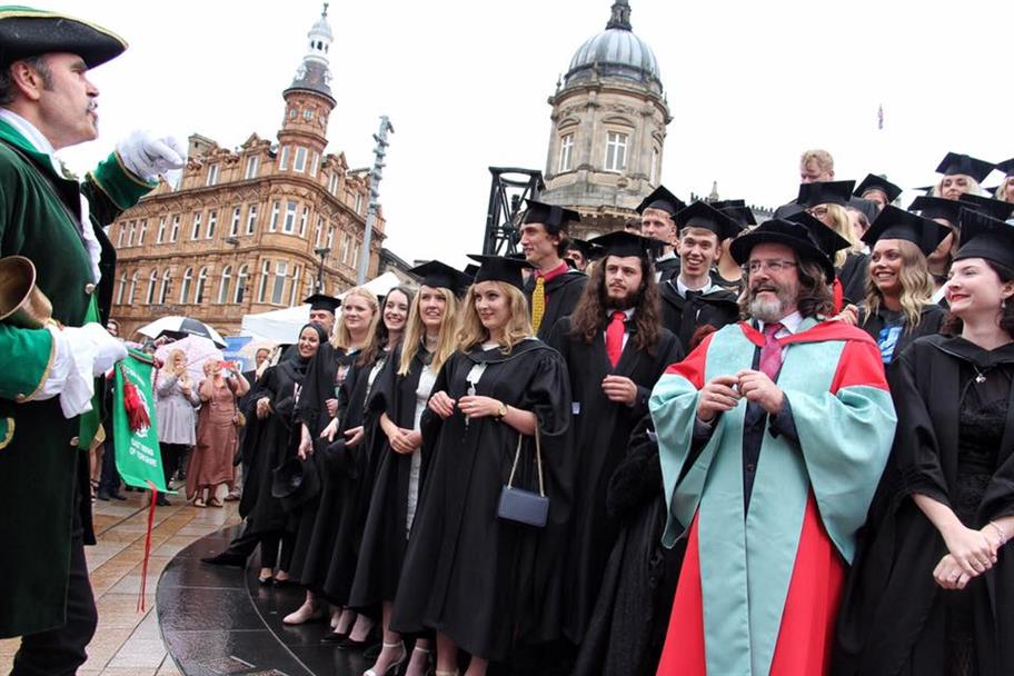 Gregory Doran in red and blue academic robes, with students