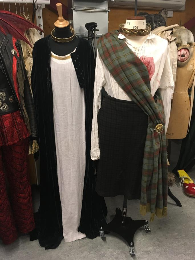 Man's and woman's costumes on tailors' dummies - bloodstained shirt with tartan scarf draped over