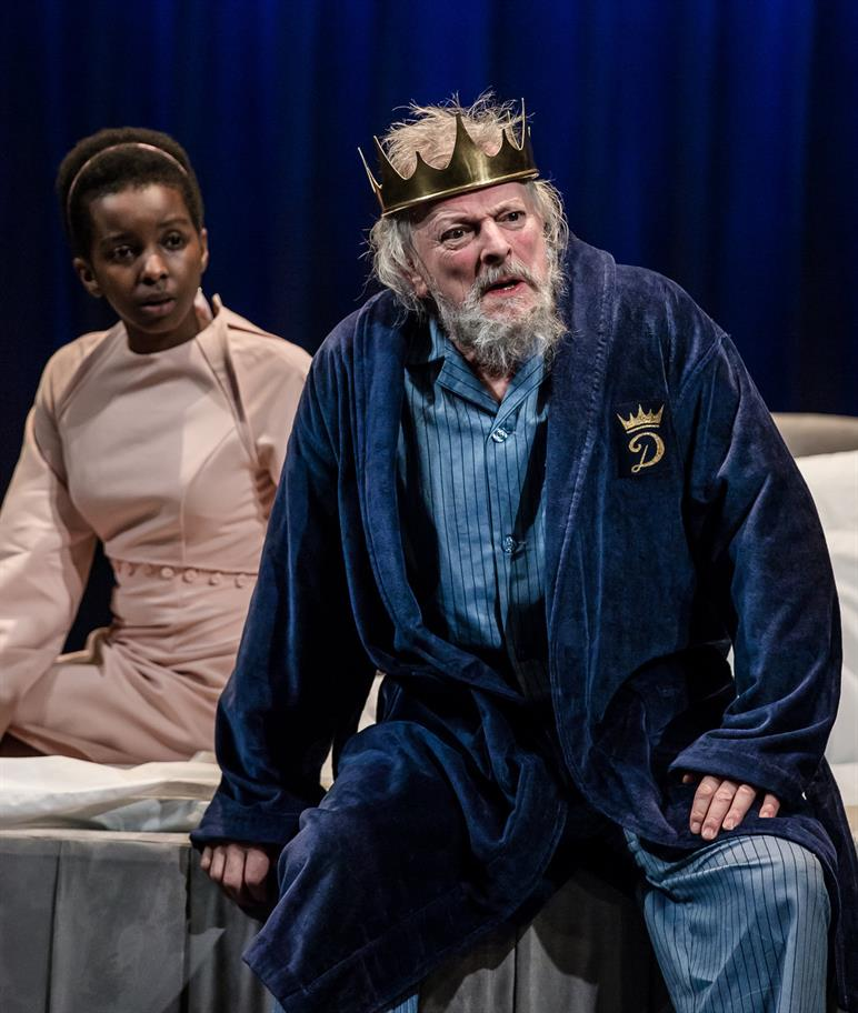 Donna Banya in a pink dress sits next to David Acton's Duncan, who wears a blue dressing gown and gold crown