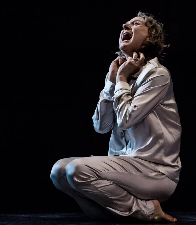 Niamh Cusack sits on the stage, screaming, in silk pyjamas.