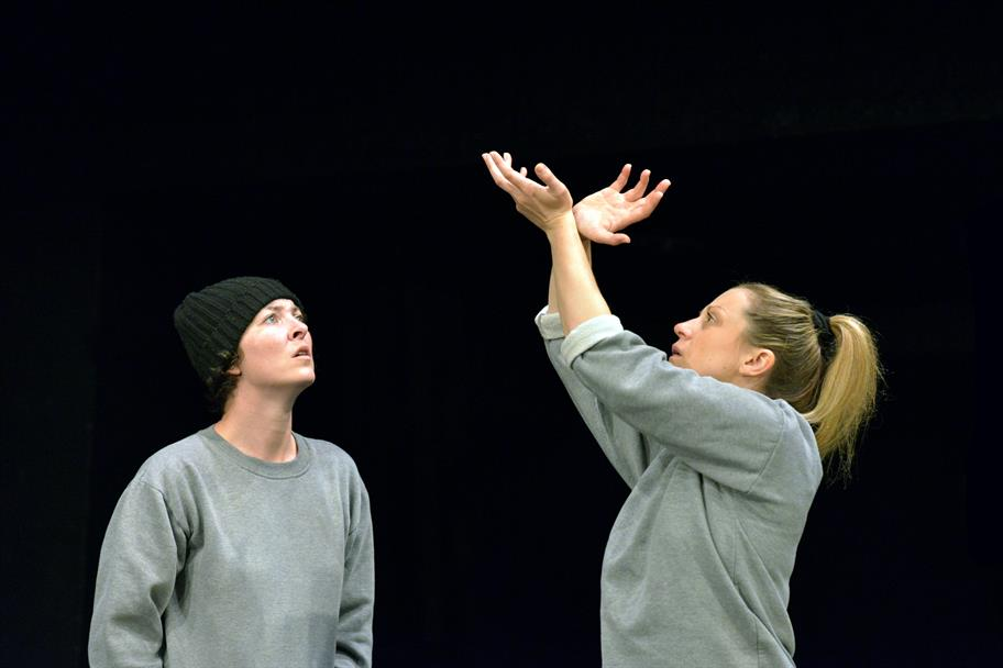 A woman in a black hat watches as another woman raises her hands in the air.