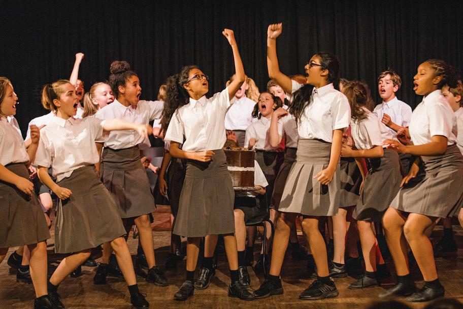 A group of schoolgirls raise their arms in the air.