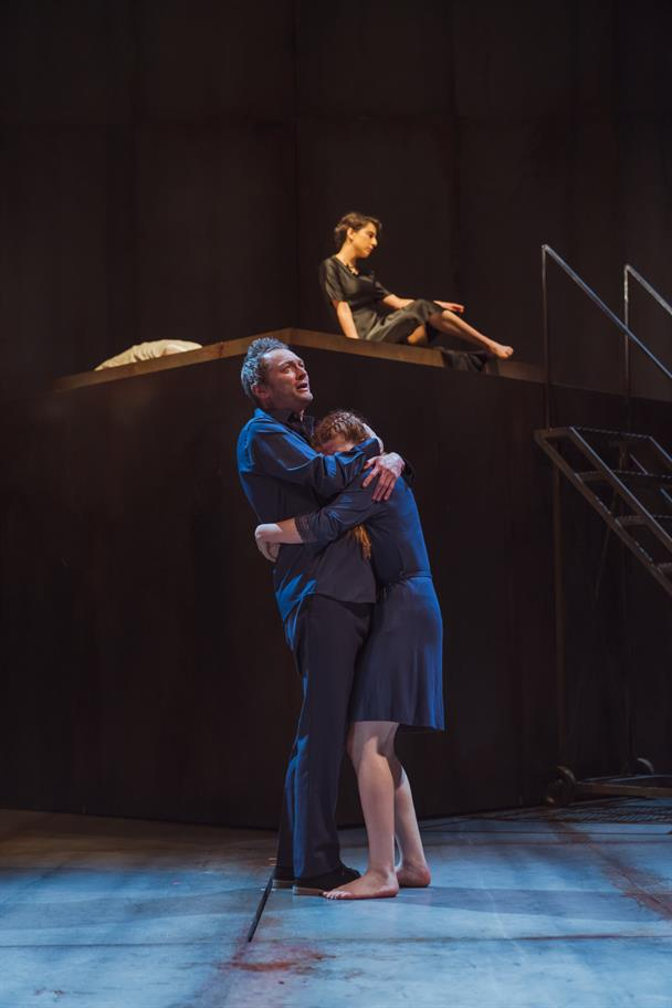 Lord Capulet hugs his daughter Juliet as Lady Capulet sits on a raised platform behind them.