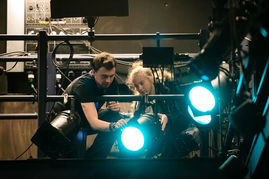 A student and a technician work on a large blue spotlight.