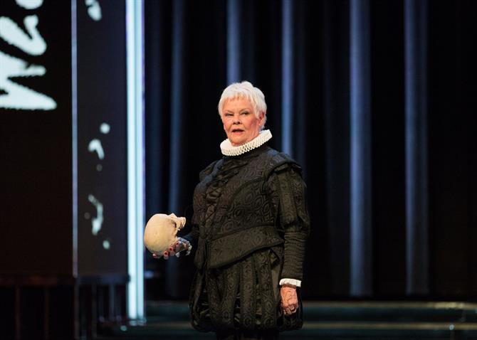 Judi Dench in costume, holding a skull.