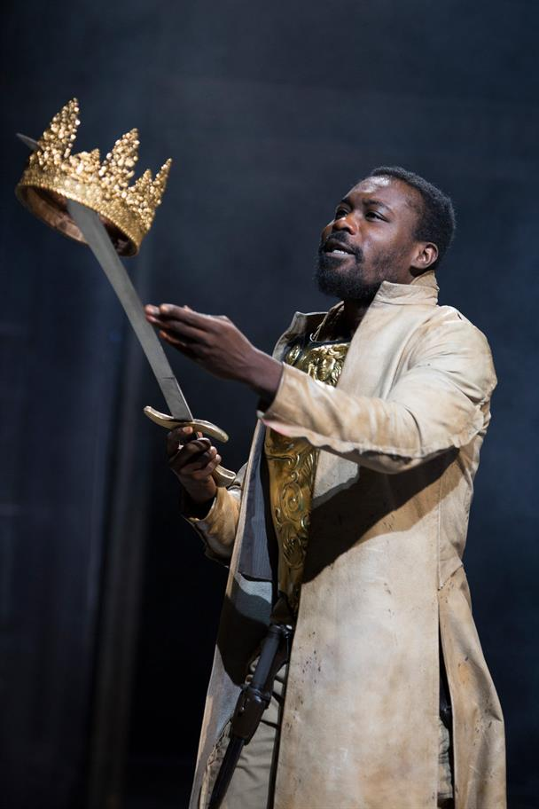 Tamburlaine holds his golden crown on the end of his sword.