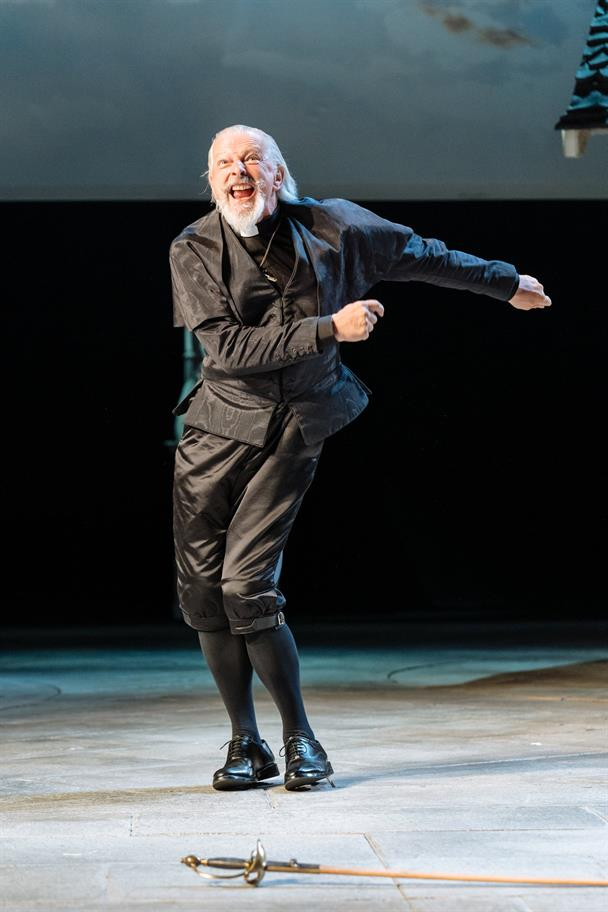 David Acton dances as Sir Hugh Evans, wearing a black outfit with a priest's collar.