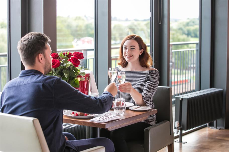 A couple toast with wine glasses at the Rooftop Restaurant