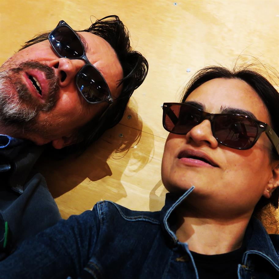 Jim and Amina lying down dressed in black leather jackets and sunglasses