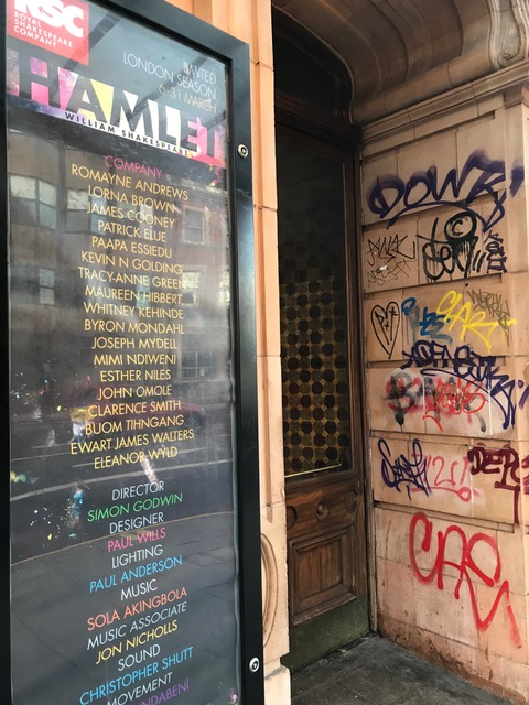 The Hamlet poster showing the full cast list, next to a wall covered in colourful graffiti.