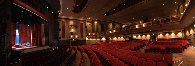 A panoramic shot of the stage and seats in the Hull New Theatre