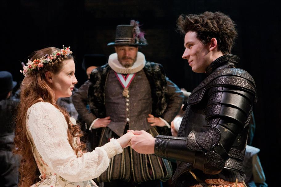 A man in black armour holds hands with a woman in a white dress.