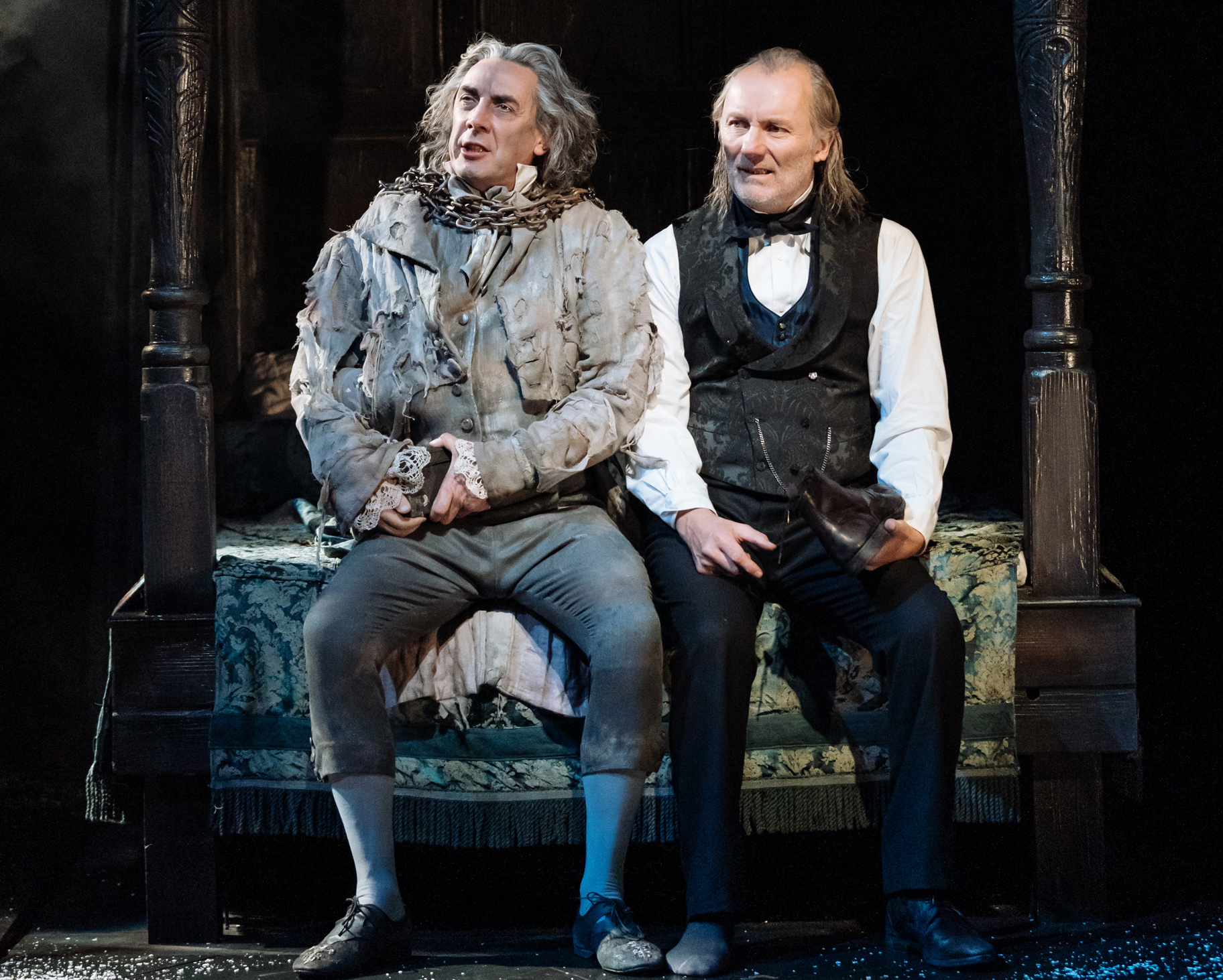 Jacob Marley and Scrooge seated on a 4-poster bed