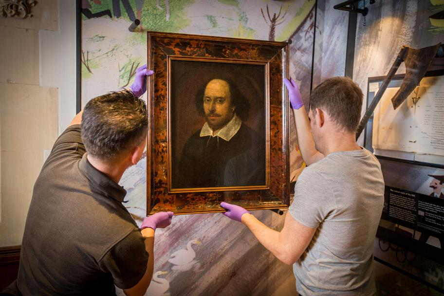 Two men in purple protective gloves hang the portrait of Shakespeare