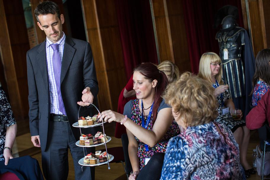 A woman takes a cake from an afternoon tea tray held by a man