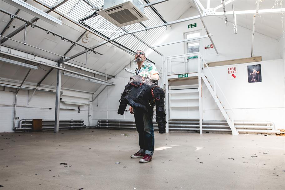 Man standing with a leather breastplate in an empty room