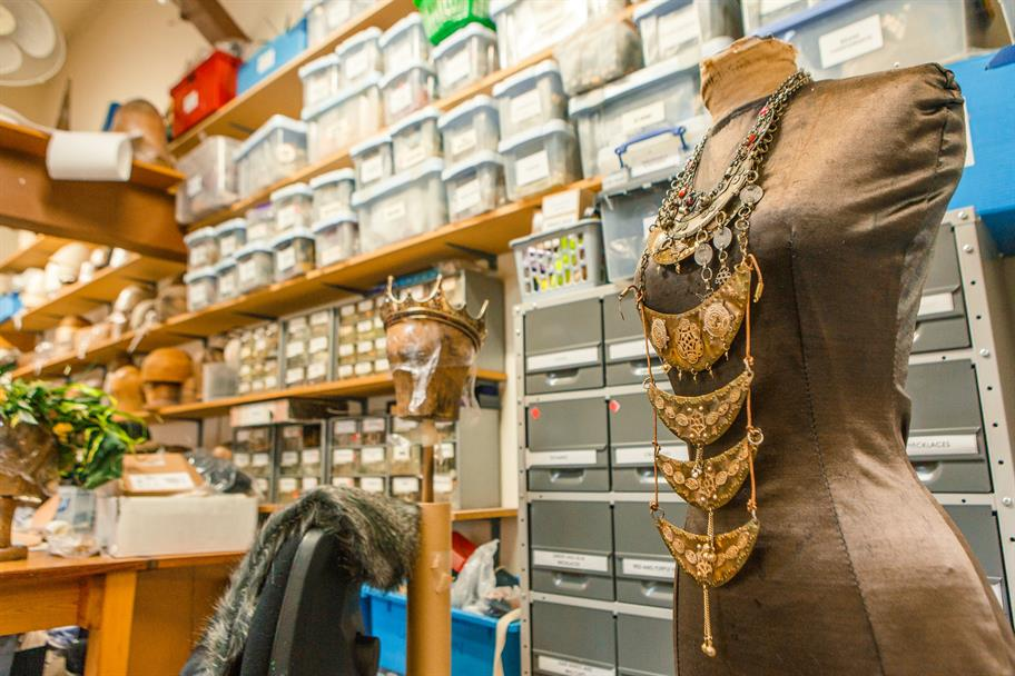 An elaborate necklace displayed on a tailor's dummy in a costume workroom