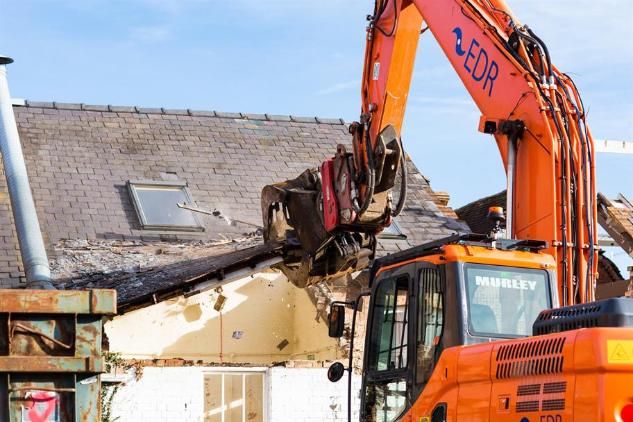 excavator tearing into the roof of a building