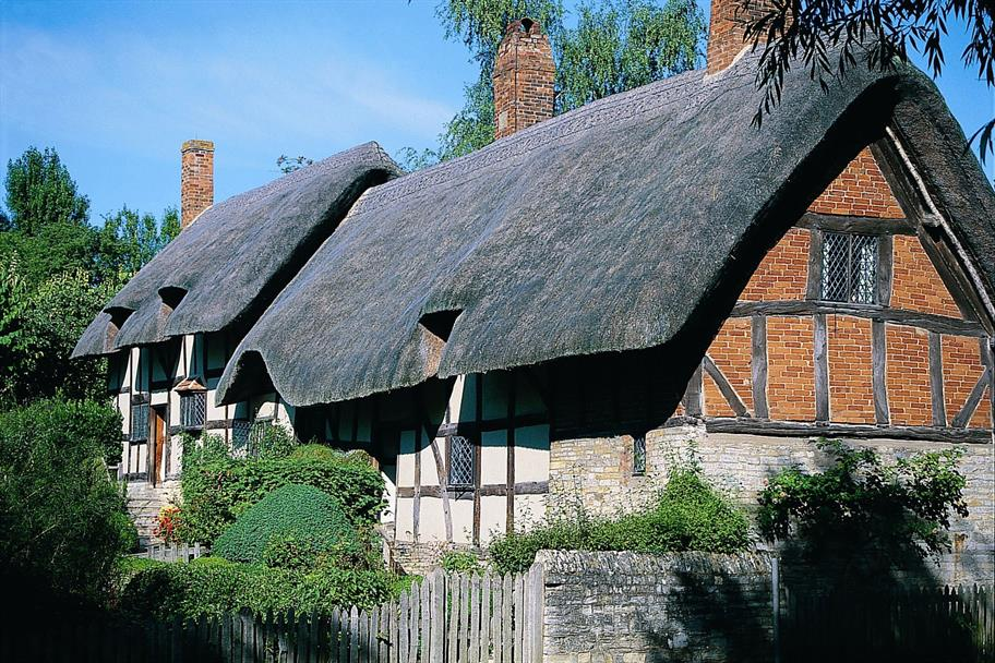 Anne Hathaway's cottage on a sunny day, surrounded by bushes and trees