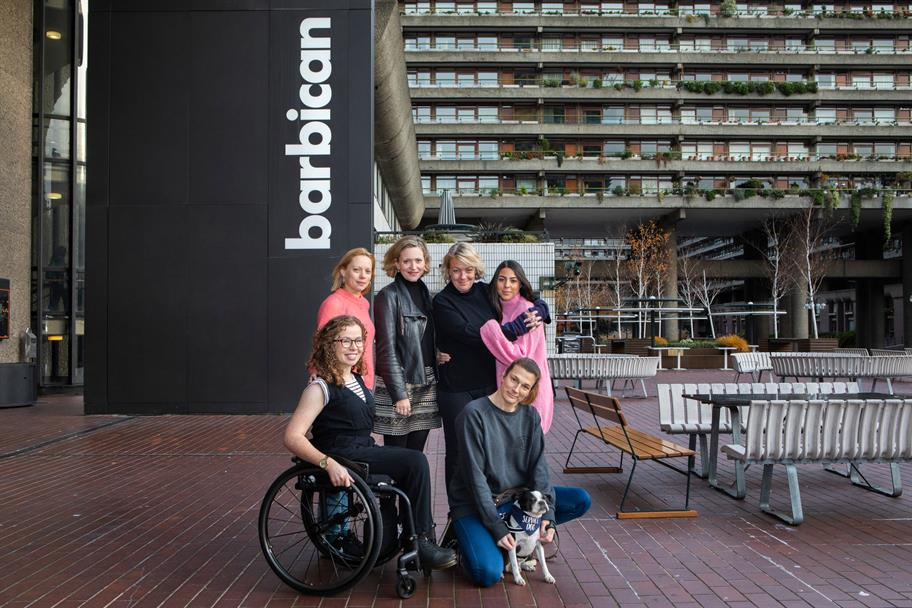 A group of actors pose outside of the Barbican Centre.