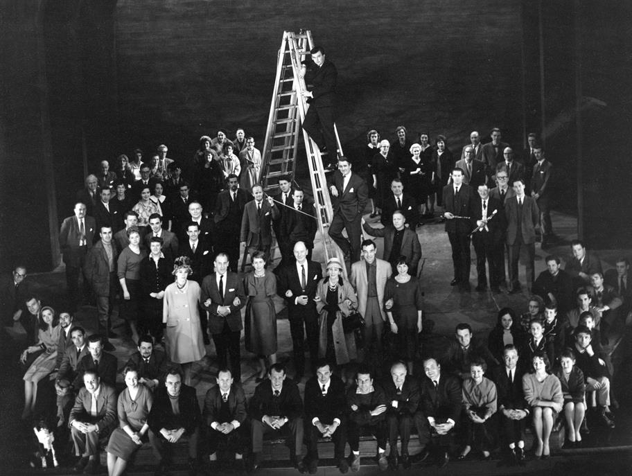 a black and white photo of a man posing at the top of a ladder, surrounded by well-dressed men and women.