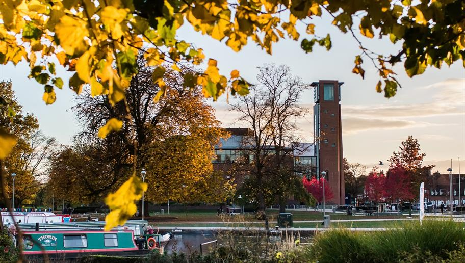 view of the Royal Shakespeare Theatre from Bancroft Gardens, with autumn leaves