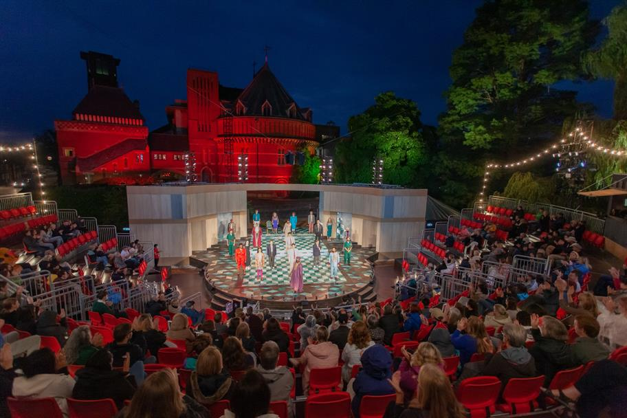 The Garden Theatre lit up at night with an audience and the cast standing to bow on the chequered stage