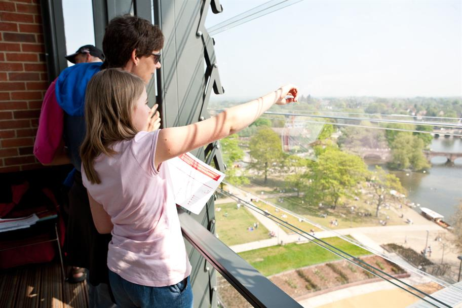 A family at the top of the tower, a little girl in a pink shirt pointing at something