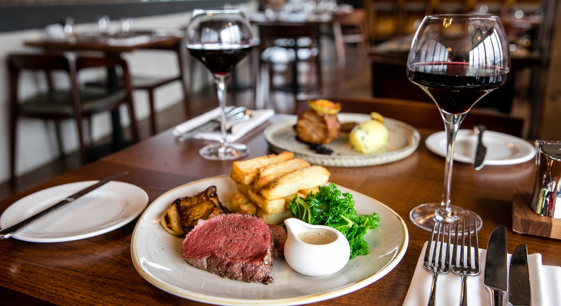 table laid with a plate of roast beef and two glasses if red wine