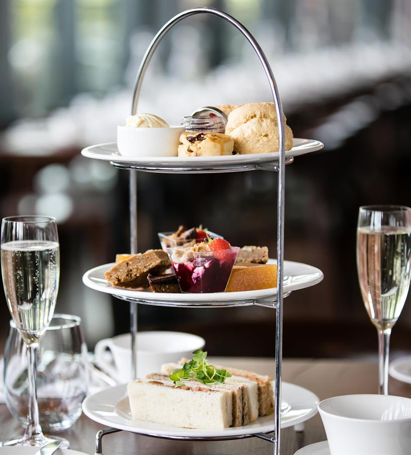 three-tiered cakes stand with cakes and sandwiches and 2 full Champagne flutes