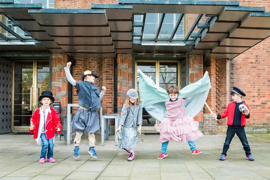 Five children in mismatched costumes outside the RST, jumping and playing