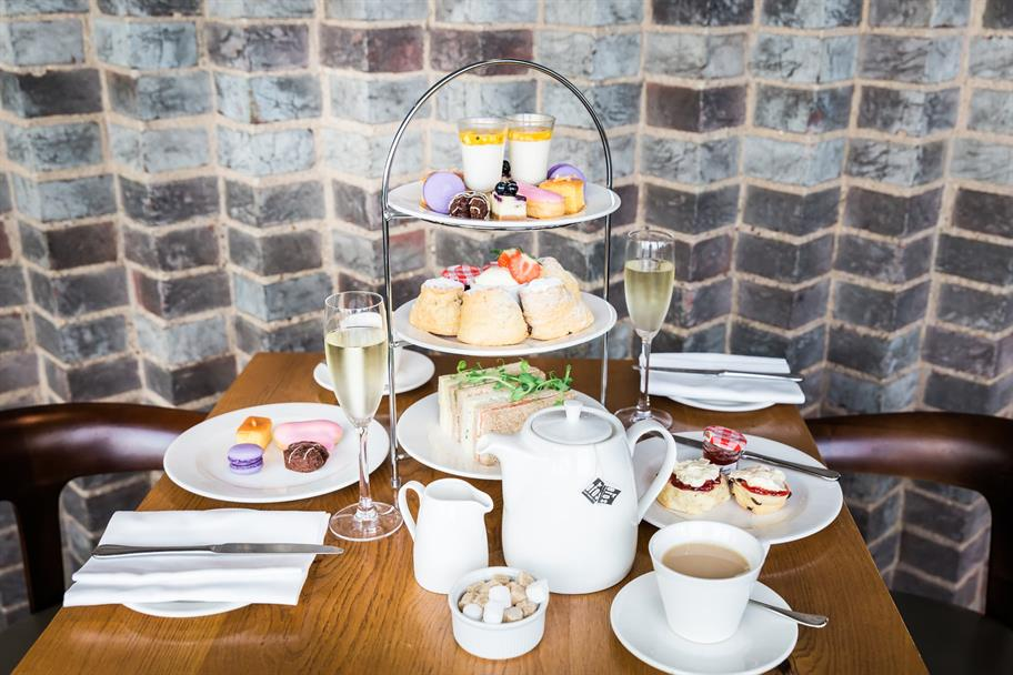 A set of afternoon tea including sandwiches, scones, colourful snacks and drinks