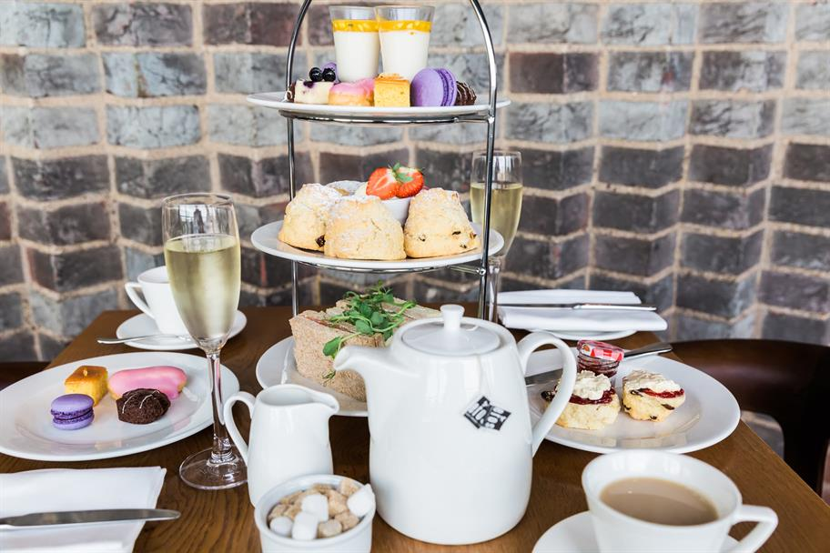 A set of afternoon tea, including scones, wine, tea, sandwiches and other colourful snacks