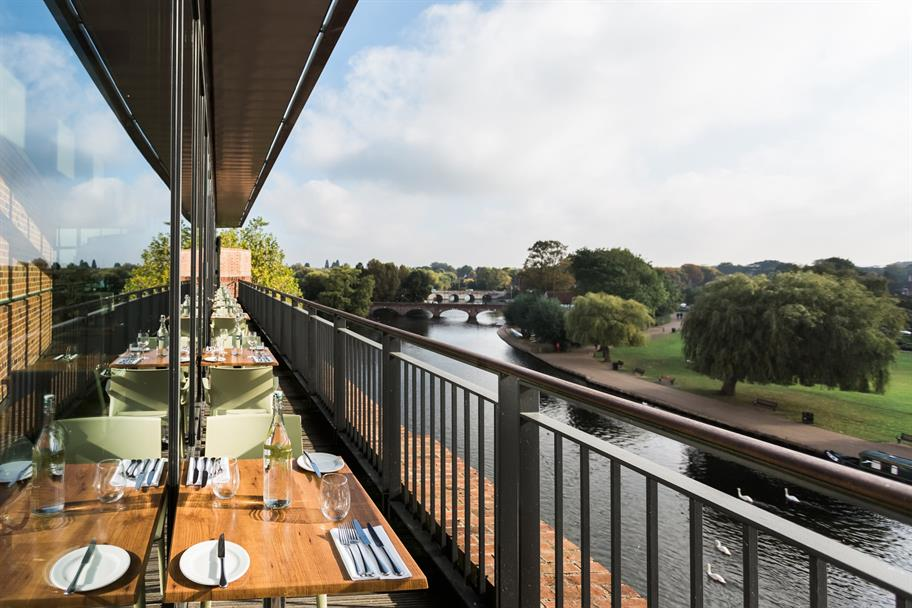 The Rooftop Restaurant  with a line of tables next to the river Avon