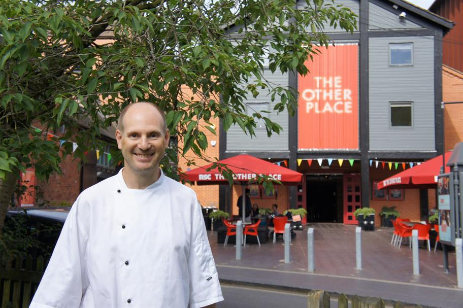 Man in white chef's jacket standing outside The Other Place smiling