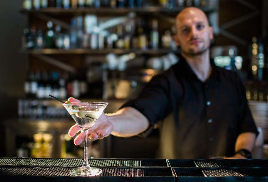 A bartender presents a glass of cocktail