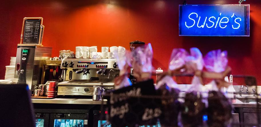 Susie's Bar showing the coffee machine and the blue neon 'Susie's sign on the left