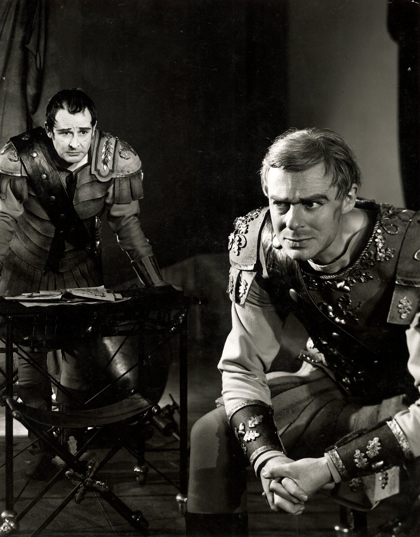 Cassius and Brutus both sit and think as they prepare for war in the 1957 production of Julius Caesar.